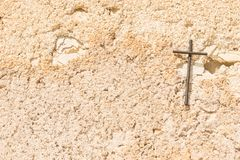 Christian cross on light brown wall background. Cemetery Cross on rustic stone wall background, religious symbol, christianity concepts stock photo