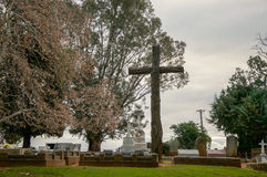 Cemetery Cross at Twilight. HENLEY BROOK,WA,AUSTRALIA-JULY 15,2016: All Saints Church cemetery with large rustic wooden cross in treed nature setting at twilight Royalty Free Stock Photos