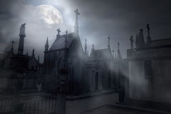 Cemetery in a foggy full moon night Stock Photo