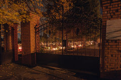 Cemetery gate. Lights of grave candles at deceased holiday Stock Images