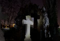 Cemetery graveyard tombstone cross night, Leuven, Belgium. Cemetery graveyard with a light painted cross and lightpainted rock, cave at night, Leuven, Belgium stock images