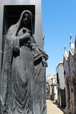 Cemetery La Recoleta. The image shows the outside of a mausoleum. Clocked women holding a cross Stock Photo