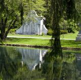 Cemetery lake reflection. Ornate marble stone mausoleum reflected in lake stock photo