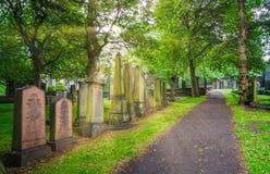 Cemetery near Parish Church of St Cuthbert in the Princes Street Gardens in a sunny summer afternoon. Edinburgh, Scotland. The Parish Church of St Cuthbert is a Royalty Free Stock Photos