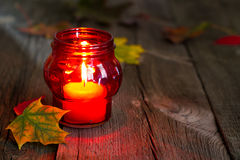 Cemetery red lantern candle with autumn leaves in night Stock Image