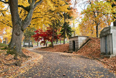 Cemetery Road Past Mausoleums in Fall Royalty Free Stock Photography