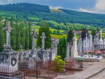 Cemetery Rolling Hills Landscape in Belgium Europe with brightly colored yellow fields and forest in Background. Detailed Royalty Free Stock Image