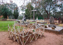 Cemetery with Rustic Cross. HENLEY BROOK,WA,AUSTRALIA-JULY 15,2016: All Saints Church cemetery with headstones, garden fences and large rustic wooden cross in Stock Photos