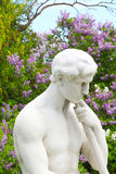 Cemetery, sculpture in front of lilac. Stone sculpture in front of beautiful lilac Stock Photo