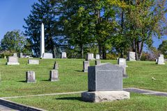 Cemetery Shot With Blank Tomb Stone in Front. Horizontal shot of a blank tombstone in a cemetary.  Green trees and blue sky behind it Stock Photo