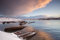Cemetery of small fishing boats in Teriberke at sunrise. Murmans Stock Image