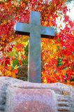 In a cemetery stands a black stone cross near a wall in autumn light stock photography