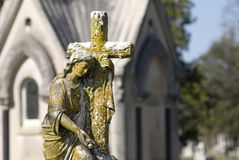 Cemetery Statue of Woman with Cross. An old cemetery statue of woman with cross church structure in background located at Mt. Olivet Cemetery in Nashville, TN Stock Images