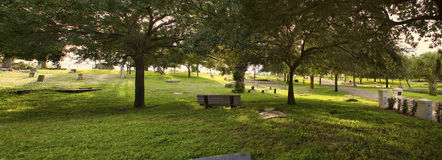 Cemetery at Sunset. Panoramic view of a hilltop cemetery in Central Florida. Sunlight is filtering through the oak trees and illuminating gravestones Stock Images