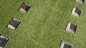A cemetery tombstone with green field
