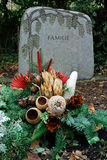 Cemetery at xmas. A tombstone with xmas flowers. The letters on the stone is the german word for family. Sandwich of two photos Stock Photography