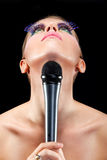 Cemetrical composition of a female singer and mic Royalty Free Stock Photos