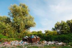 Cemitério de automóveis na natureza de então - recipientes completos do lixo - nenhuma separação imagens de stock