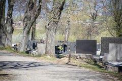 Cemitério no dia ensolarado Sepulturas com flores e velas foto de stock royalty free