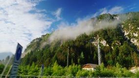 Cenário bonito de Áustria, vista de uma janela de um trem ou de um carro movente Montanhas altas cobertas com a floresta e as nuv filme