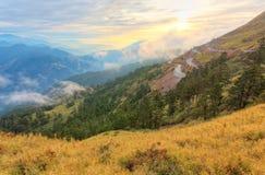 Cenário bonito do por do sol com uma estrada da montanha que curva-se altamente acima na escala alpina do ` s de Taiwan que condu Fotos de Stock Royalty Free