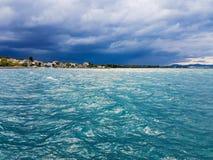 Cenário bonito em Oropos Grécia com a vila contra o mar e um céu dramático Foto de Stock Royalty Free