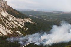 Cenário bonito, nuvens que rodam entre montanhas e árvores Fotos de Stock Royalty Free