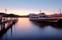 Cenário da manhã da lucerna do lago no nascer do sol com ideia de um estacionamento do navio de cruzeiros por uma doca de madeira Fotografia de Stock Royalty Free