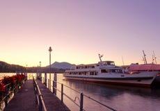 Cenário da manhã da lucerna do lago no nascer do sol com ideia de um estacionamento do navio de cruzeiros por uma doca de madeira Fotografia de Stock