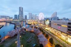 Cenário da noite da área de Yokohama Minatomirai, com vista de arranha-céus altos da elevação no fundo, uma roda de Ferris gigant fotografia de stock royalty free