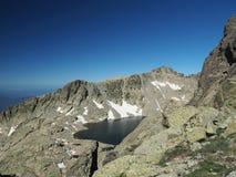 Cenário das montanhas altas com neve do lago e picos afiados Imagens de Stock