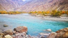Cenário de relaxamento de claro - água claro azul do rio de Gilgit com as montanhas rochosas vermelhas no outono de Paquistão fotografia de stock royalty free