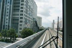 Cenário de um trem que viaja no trilho elevado da linha de Yurikamome no Tóquio fotos de stock royalty free
