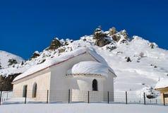 Cenário do inverno de uma capela coberta com a neve Imagem de Stock