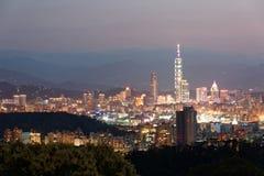 Cenário do por do sol de Taipei do centro, capital vibrante de Taiwan, com a torre do marco 101 que está para fora entre prédios Fotografia de Stock