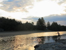 Cenário do rio com pesca do homem novo pelo crepúsculo Imagens de Stock Royalty Free