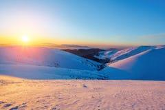 Cenário fantástico com as montanhas altas na neve e um nascer do sol no dia de inverno frio foto de stock