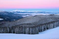 Cenário fantástico com as montanhas altas na neve, na névoa textured densa e em um nascer do sol no dia de inverno frio fotografia de stock