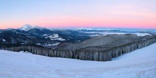 Cenário fantástico com as montanhas altas na neve, na névoa textured densa e em um nascer do sol no dia de inverno frio foto de stock