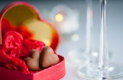 Cenário romântico com corações do chocolate em uma caixa coração-dada forma vermelha Foto de Stock Royalty Free