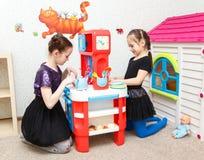 两个小女孩打与玩具厨房的角色比赛在日托cen中 免版税图库摄影