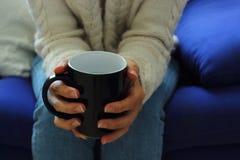 Cena acolhedor Jovem mulher com a xícara de café nas mãos imagem de stock