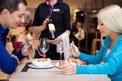 Cena agradable en un restaurante - el camarero ofrece el vino Imagen de archivo