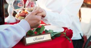 Cena al aire libre romántica de los pares que llevan a cabo las manos Tabla adornada con la placa reservada y la rosa del rojo Ni almacen de metraje de vídeo