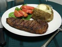 Cena asada a la parilla del filete con los utensilios Foto de archivo libre de regalías