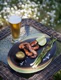 Cena asada a la parrilla conjunto de los camarones en jardín Imagen de archivo