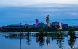 Cena azul da noite da hora das reflexões da inundação do Rio Missouri das construções em 2019 do parque de estacionamento do casi foto de stock