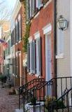 Cena bonita da rua com as bandeiras que penduram as casas exteriores que alinham ruas de pedrinha, cidade velha, Alexandria, Va,  Imagem de Stock