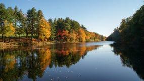 A cena bonita das árvores coloridas do outono refletiu na água de um rio durante o outono em Massachusetts imagem de stock royalty free