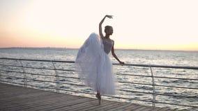 Cena bonita de um dançarino de bailado perto da barra transversal que estica seus pés, pas clássico praticando Opinião do fuzilei filme